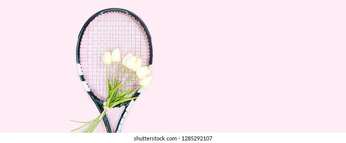 tennis love layout on pastel pink background with tennis racket with bouquet white tulips flowers. Women's Day March 8. Copy space. Valentine's day concept with tennis play. Flat lay, horizontal.