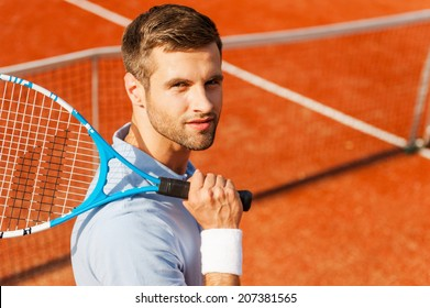 Tennis is my life! Top view of happy young man in polo shirt carrying tennis racket on shoulder and smiling while standing on tennis court