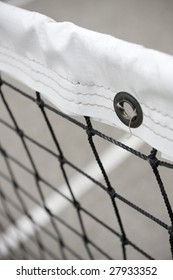 Tennis Net. Close-up of tennis net with white line on court visible in background. Vertical format.