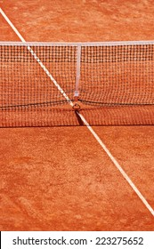 Tennis net detail on a clay court