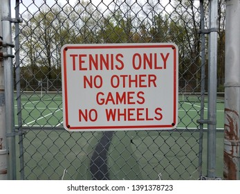 tennis only no other games no wheels sign on metal fence at tennis court
