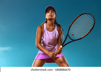 Tennis player. Beautiful girl teenager and athlete with racket in pink sporswear and hat on tennis court. Fashion and sport concept.