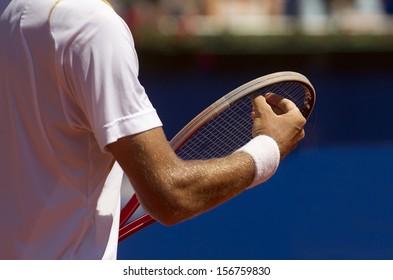 A tennis player checks racquet for serve a tennis ball during a match