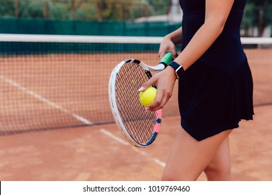 Tennis player. Close-up photo of athlete woman in sportswear holding racket and ball, playing tennis on the court.