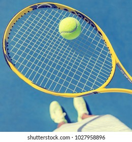 Tennis player girl taking pov selfie of racket and ball ready to play holding racket and showing shoes on blue outdoor tennis court. American hard court.