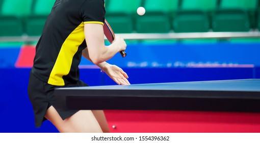 Tennis player hits a white tennis ball