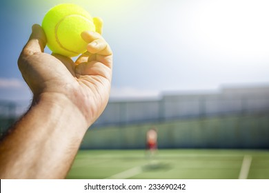 Tennis player holding the ball and getting ready to serve.