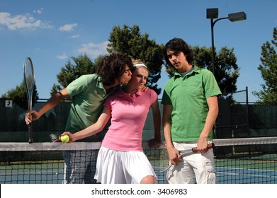 A tennis player kissing a girl while his twin brother watches