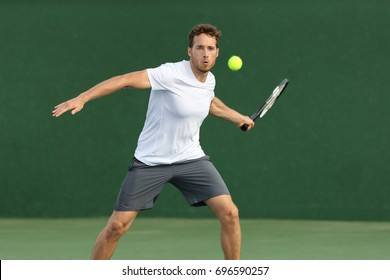 Tennis player man hitting ball with racket on green background. Sports athlete training forehand grip technique on outdoor court.