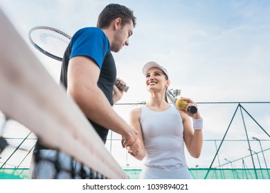 Tennis player man and woman giving handshake after match at the net