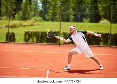 Tennis player on tennis court hitting ball