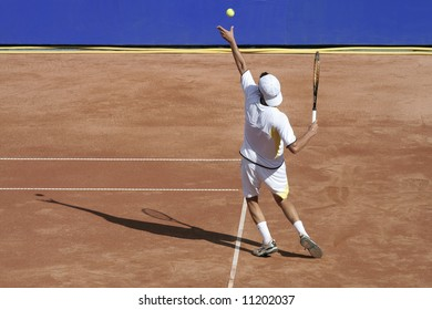 Tennis player on hard court serving the ball