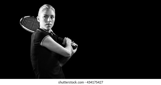 Tennis player playing tennis with a racket on black background
