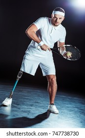 tennis player with tennis racket and ball in hands looking at camera