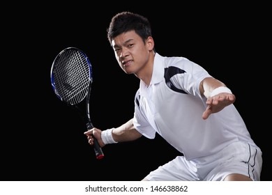 Tennis player ready to hit ball, portrait