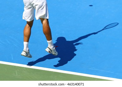 Tennis player serves the ball (shadow of player on the hard court)