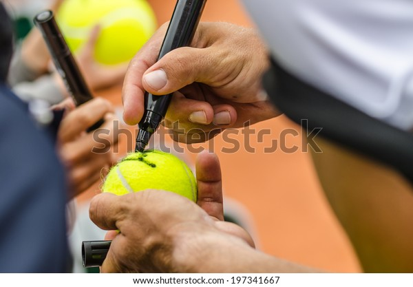 Tennis player signs autograph on a tennis ball after win, closeup photo showing tennis ball and hands of a man making signature.