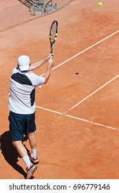 A tennis player strikes the ball, a back view