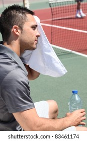 tennis player sweeping out the sweat from his forehead
