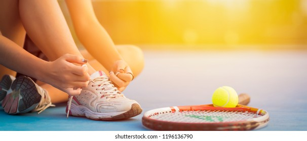 Tennis player tying shoelaces in court. sunset banner panoramic crop for copy space.
