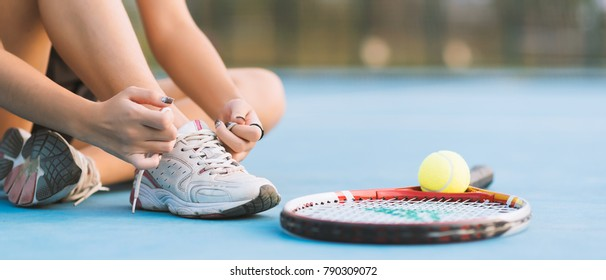 Tennis player tying shoelaces in court. vintage tone banner panoramic crop for copy space.