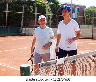 tennis players of different generations talking on court playing tennis