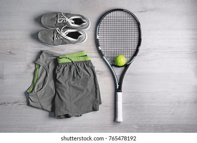 Tennis racket, ball, clothes and shoes on wooden background