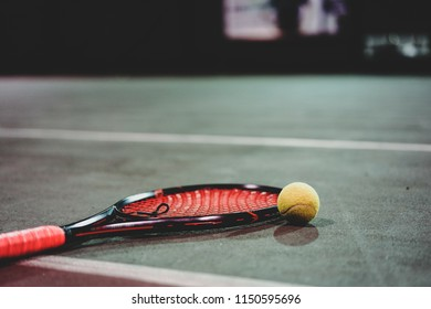 tennis racket and ball lying on the court
