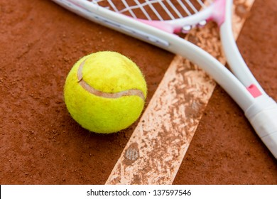 Tennis racket with ball lying on the floor of a clay court