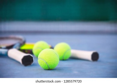 Tennis racket with ball on blue hard court with nobody - tennis sport background concept