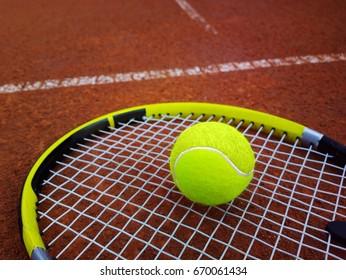 tennis racket with a tennis ball on a tennis court