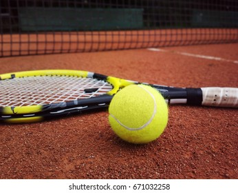 tennis racket with a tennis ball on a tennis court