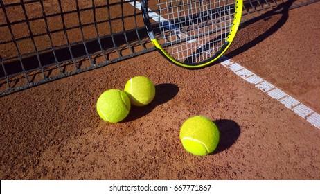 tennis racket with tennis balls on a tennis court