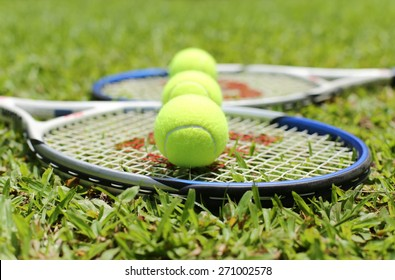 Tennis racket with balls on the grass in blur background