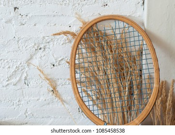 Tennis racket Brown With hay There are white walls as background.