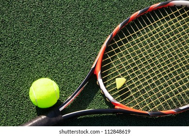 A tennis racket and new tennis ball on green court