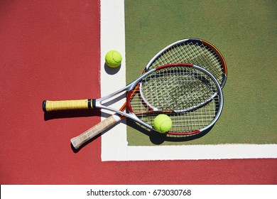 A tennis racket and new tennis ball on a freshly painted tennis court.