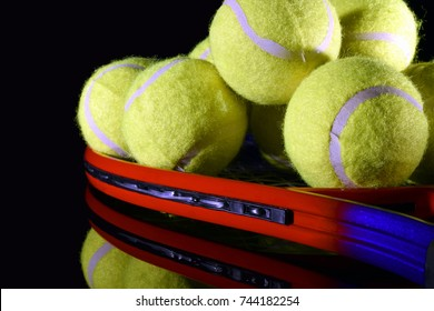 Tennis racket and pile of tennis balls on black reflective surface. Horizontal close up image.