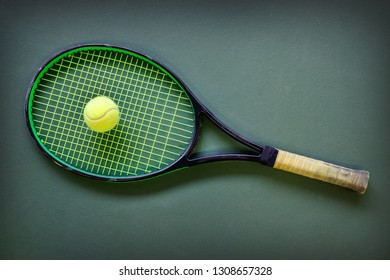 Tennis racket racquet and ball lying on the ground in indoor court