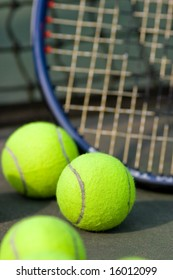 A tennis racket is resting against a net on a tennis court surrounded by tennis balls.  Vertically framed shot.