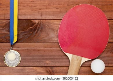 Tennis rackets and balls of plastic on a wooden table