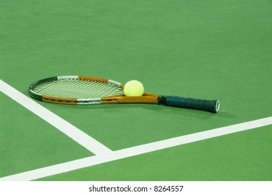 Tennis racquet and ball on tennis court under fluorescent lights at night, ideal for desaturation to black and white