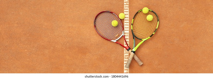 Tennis racquets with tennis balls on clay court