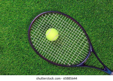 A tennis raquet or racket and yellow ball on grass.
