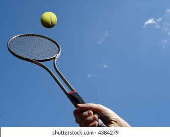 Tennis return with racket against blue sky.