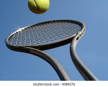 Tennis serve with racket against blue sky.