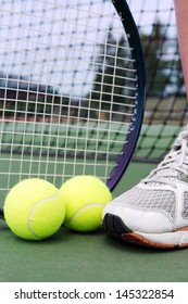 Tennis shoe, racket and balls on a hard court in front of net.