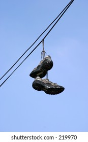 tennis shoes hang from power line wires, marking gang territory in los angeles