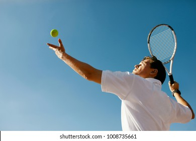 Tennis Sport. Man Playing Tennis Outdoors. Portrait Of Attractive Young Man In White T-shirt With Racket And Ball On Sky Background. Active Lifestyle. High Quality Image.