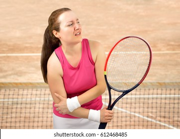 tennis woman player with elbow injury holding the racket on a clay court